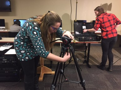2013-14 President Brianna Kelly sets up her photography equipment with current President Emily Brosious.