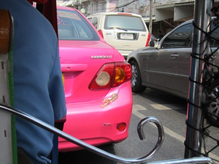 Pink taxi with tiger sticker.