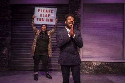 """A man speaks and woman holds a sign that reads """"please clap for him"""""""