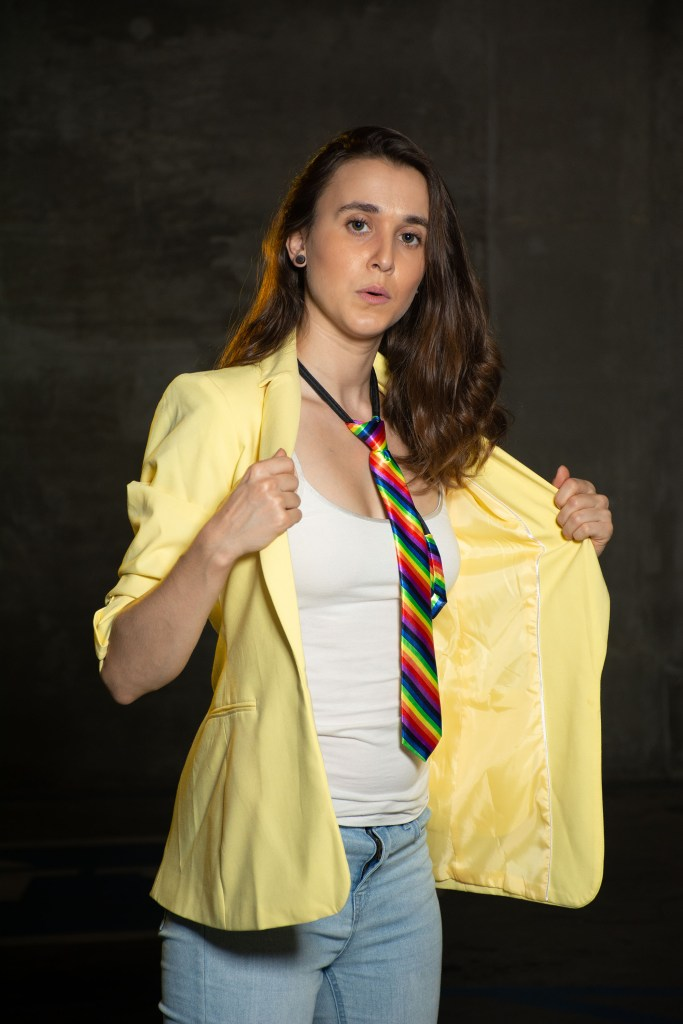 Woman in a rainbow tie and yellow button down shirt