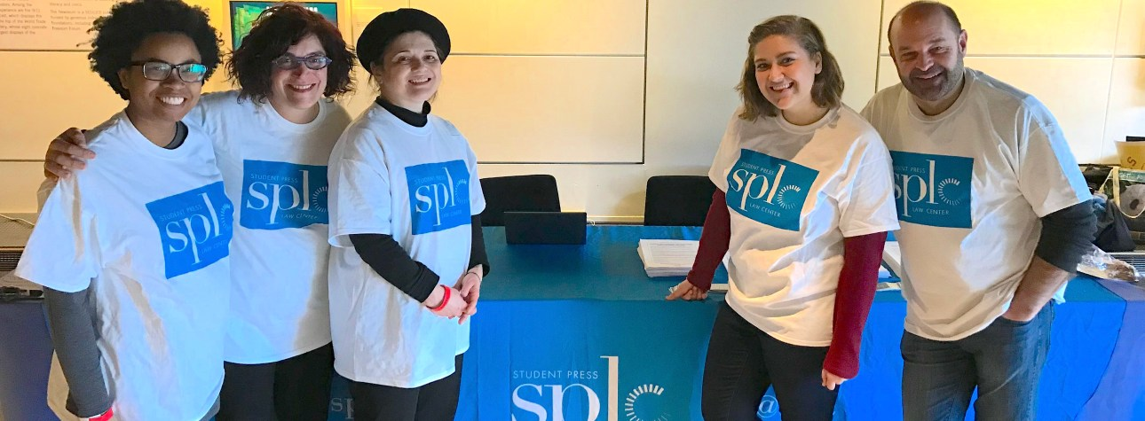SPLC staff in front of an SPLC booth