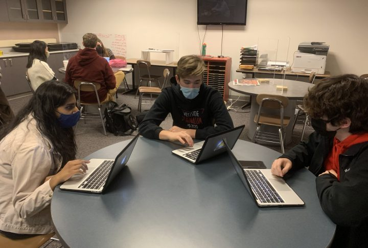 Three high school students wearing face masks work at laptops at a table.