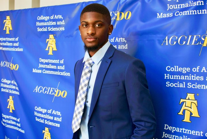 Jarod Hamilton, a Black college student and EIC of The Register poses in front of a blue background