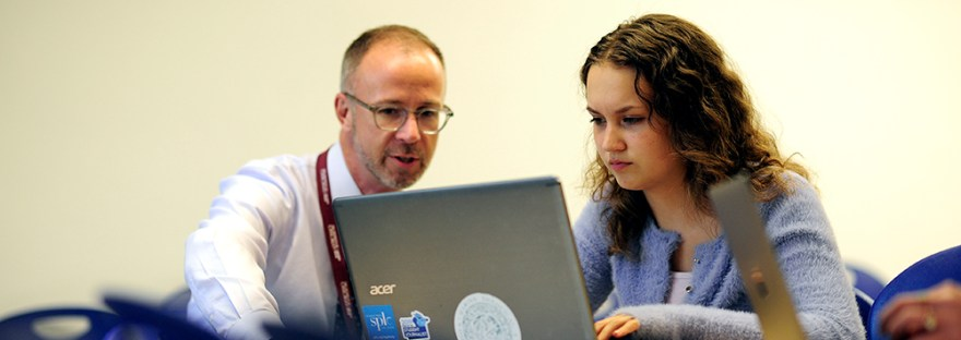 Teacher and student sit in front of a grey laptop talking