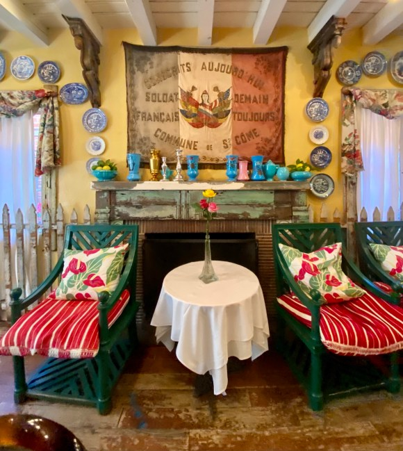 Green chairs with striped and floral cushions, French Flag, fireplace mantel with patina