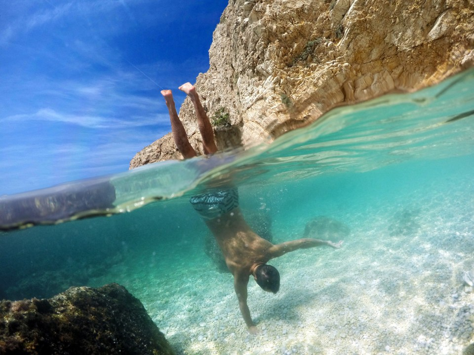 Man in boardshorts doing handstands in the sea over under photo