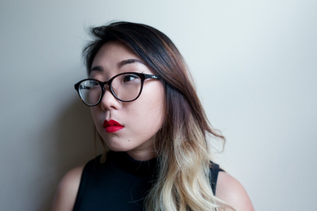 Photo of Franny Choi. She is a young Asian woman. Franny has long hair that is dark brown at the top and becomes lighter, eventually blonde at the bottom. She stand against a white backdrop, looking off into the distance.She wears glasses and a black tank top, and has bright red lipstick.