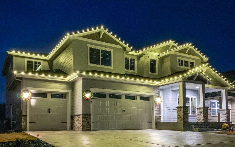 A two story Spokane home lined with warm, white Christmas lights. Both stories of the home are lined with lights.