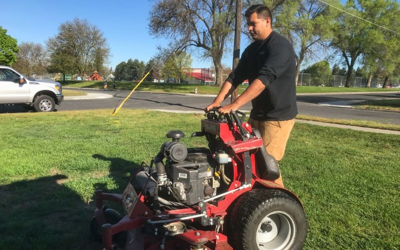 A Spokane's Finest Lawns employee using a commercial mower during a grass cutting service.