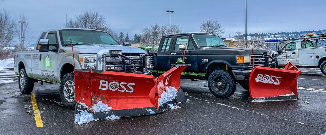 2 snow plow trucks in a parking lot with Spokane's Finest Lawns graphics on them.