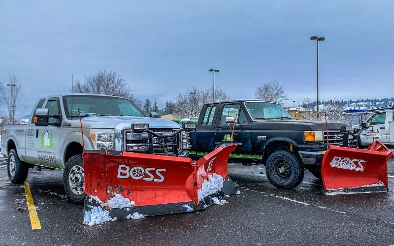 Two Spokane's Finest Lawns work trucks outfitted with snow plows.