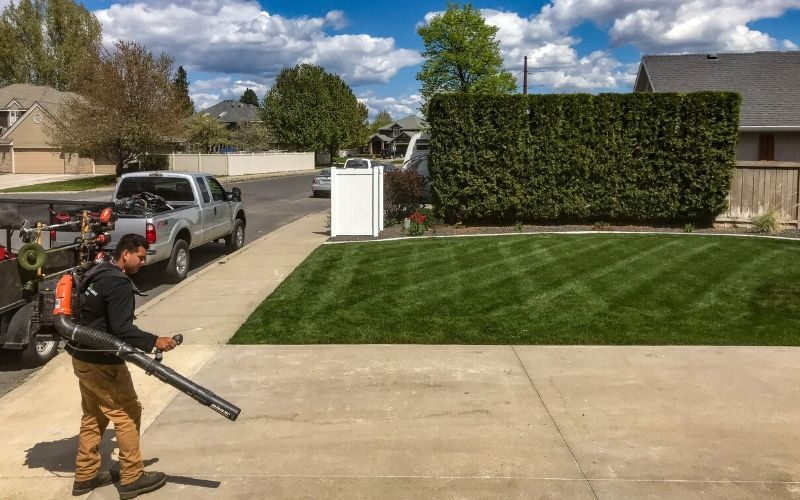 A Spokane's Finest Lawns employee clearing a driveway of all clippings after a grass cutting service.