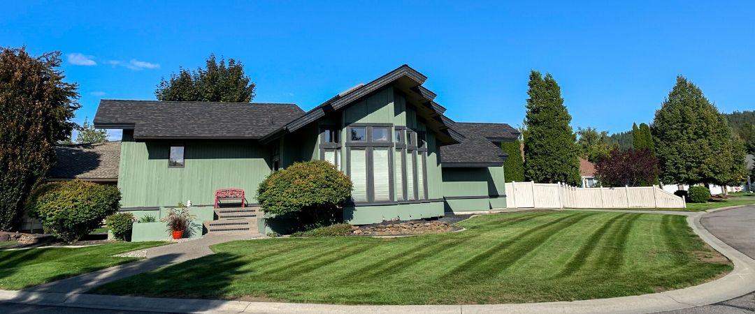 A residential Spokane home with a recently mowed lawn. The sky is bright blue and cloudless and the grass is green and has visible mowing stripes.