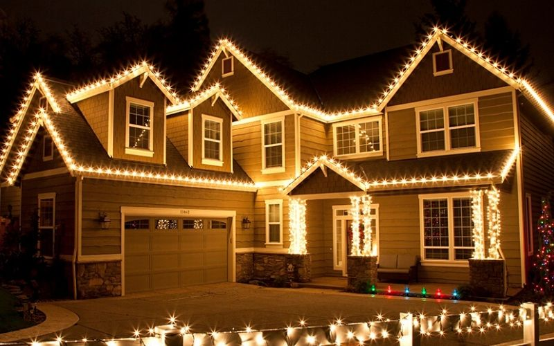 A two story home lined with warm yellow Christmas lights. Both stories and the porch are lined with lights.
