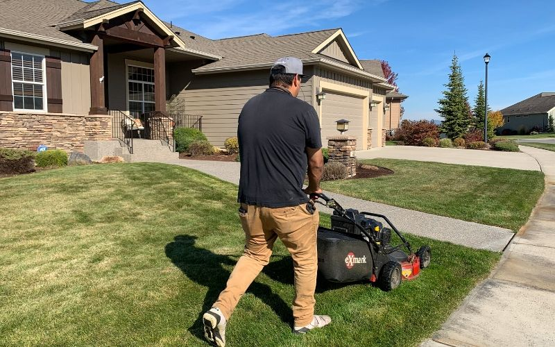 A Spokane's Finest Lawns employee using a push mower to mow a small lawn.