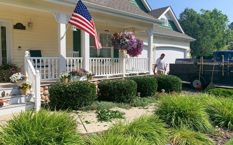 A Spokane's Finest Lawns employee trimming shrubs along a porch.