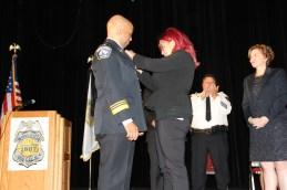 Nyasia Arradondo pins the Chief's Badge on her father Chief Arradondo
