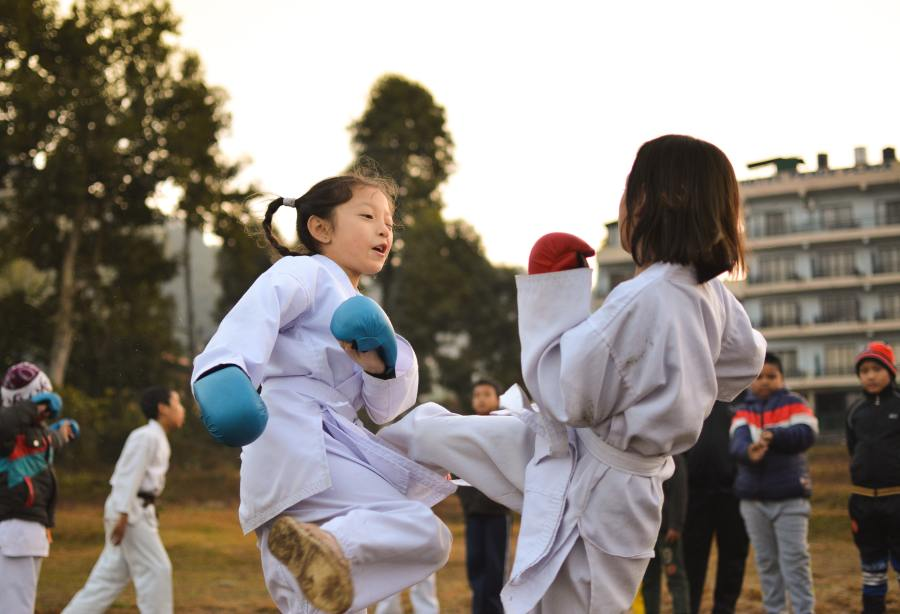 Two young girls practice martial arts.