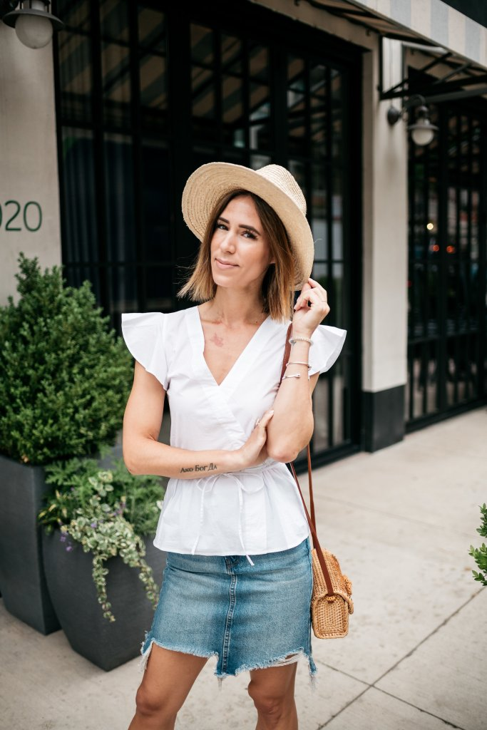 Seattle Fashion Blogger wearing white blouse and distressed denim skirt with summer straw hat