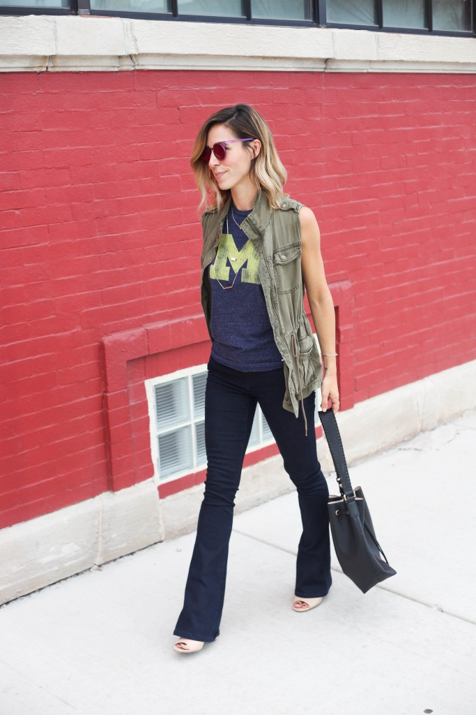 House of Holland Cagefighter sunglasses, Black bucket bag, University of Michigan Muscle Tee, Game day fashion, game day fashion ideas, what to wear to a football game, Olive khaki Vest, Nude open-toe mules, Henry & Bell Micro Flare Denim, University of Michigan, Michigan Wolverines