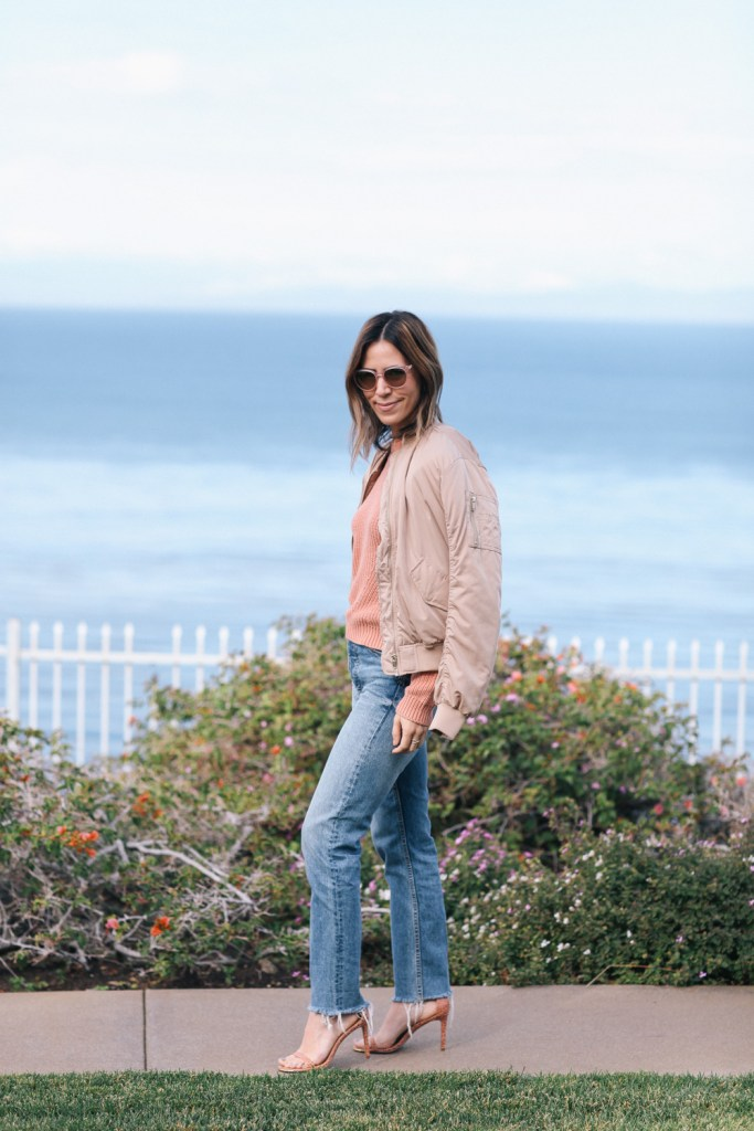 Peach bomber jacket with high-waisted denim and nude sandals