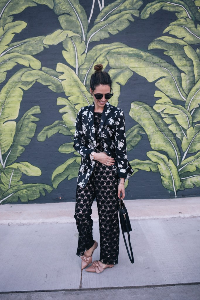 Blogger Mary Krosnjar wearing lace jumpsuit and floral blazer from Rent the Runway