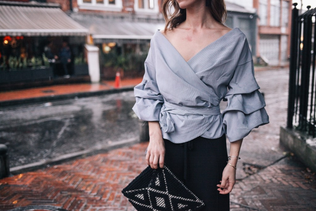 Blogger Mary Krosnjar wearing ruffled sleeved top and Sole Society Tasseled Woven Clutch