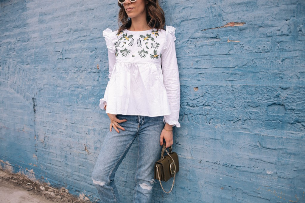 Blogger Mary Krosnjar wearing White Embroidery Ruffle Trim Pleated Blouse and distressed denim
