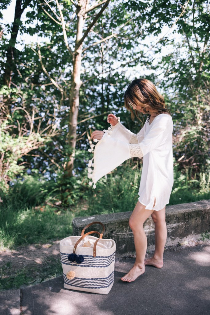 Blogger Mary Krosnjar wearing white beach cover-up and striped beach bag