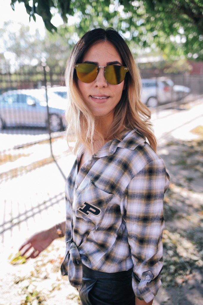 Blogger Mary Krosnjar wearing Spitfire Gold Mirrored Sunglasses and plaid Purdue University flannel