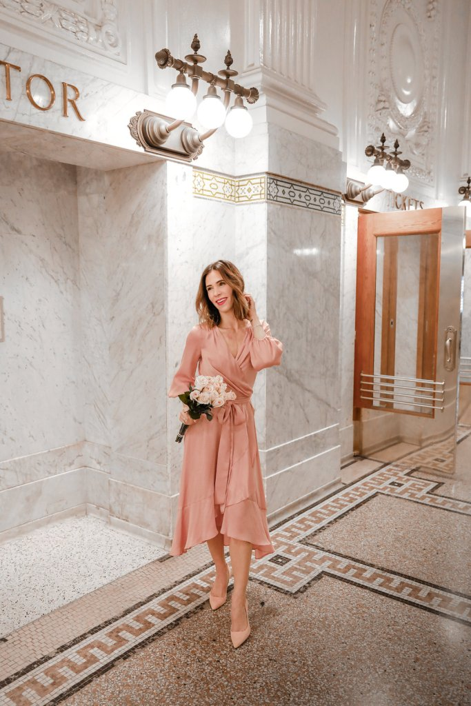 Blogger Sportsanista wearing pink silk wrap dress and pink suede pointy toe pumps