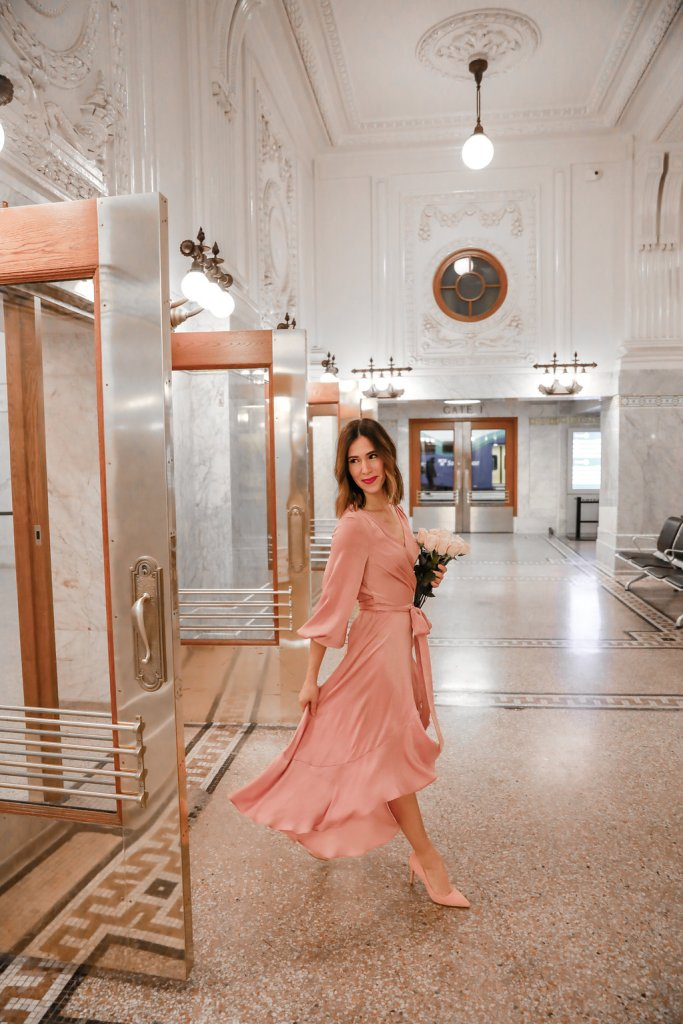 Blogger Sportsanista wearing Gal Meets Glam pink silk wrap dress and Pink Suede Pumps