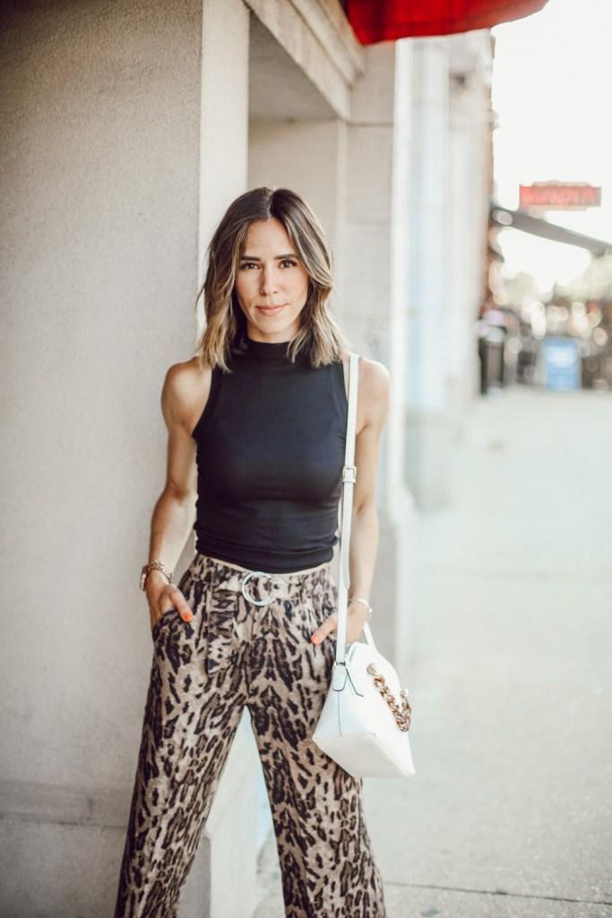 Fashion Blogger Sportsanista wearing a black mockneck sleeveless turtleneck and wide leg leopard pants for work