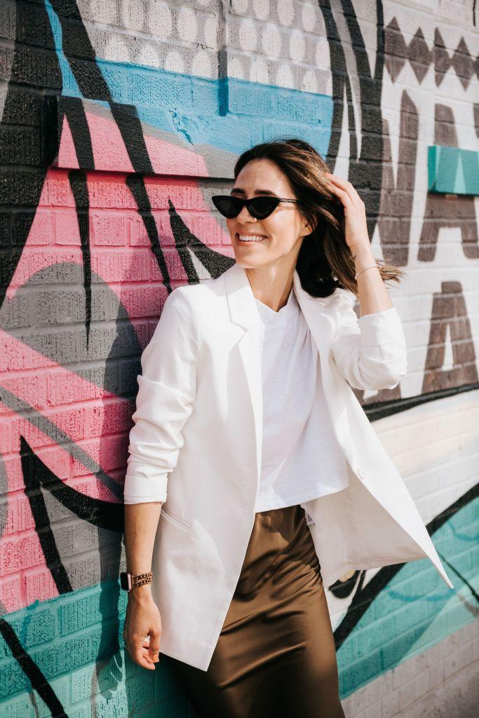 Fashion Blogger Sportsanista wearing white oversized blazer, white cropped top and slip skirt for easy summer look
