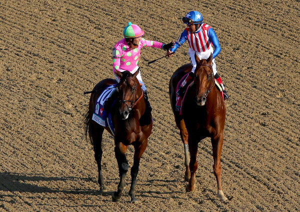 Gary Stevens (to the left aboard Firing Line) and Martin Garcia (to the right aboard Dortmund) congratulate each other after the 2015 Kentucky Derby (Elsa/Getty Images North America)