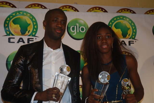 WINNERS ALL : Asisat Oshoala (right) clutching the 2014 Glo/CAF Award for African Woman Footballer of the Year and the African Youth Player of the Year Awards and Four-time winner of the Glo/CAF African Footballer of the Year Award, Yaya Toure (left) moments after receiving the awards at the Glo/CAF Awards at Eko Hotel, Lagos, Nigeria