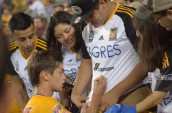 players sing autographs after the game