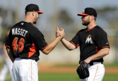 Miami Marlins pitchers Preston Claiborne, right, and Nick Masset shake hands after warming up during spring training baseball practice Sunday, Feb. 22, 2015, in Jupiter, Fla. (AP Photo/Jeff Roberson)