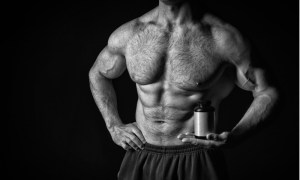 A muscular, shirtless man holds a bottle of supplements, illustrating the effects of SARMs.