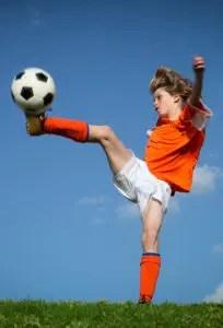 Child kicking playing football.