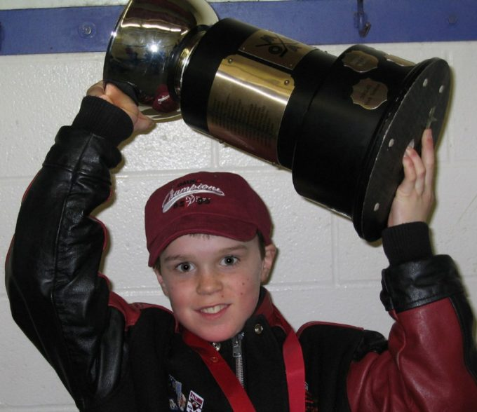 Young Connor McDavid lifting a trophy