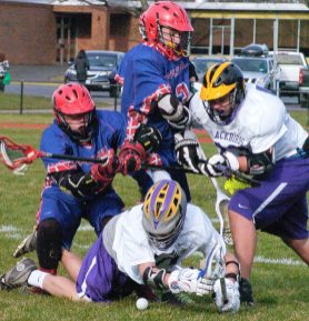 Voorheesville and Maple Hill players battle for a ground ball. Rob Jonas/Spotlight