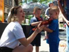 A pair of young musicians take their first violin lessons during Troy River Fest on Saturday, June 18.
