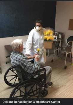 A patient at Oakland Rehabilitation and Healthcare center gets a rose