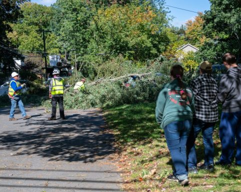 Debbie Henry and her two children watch as crews clean up a tree that fell on her car at the corner of Delsmere and Kenwood avenues in Bethlehem (Jim Franco/Spotlight News)