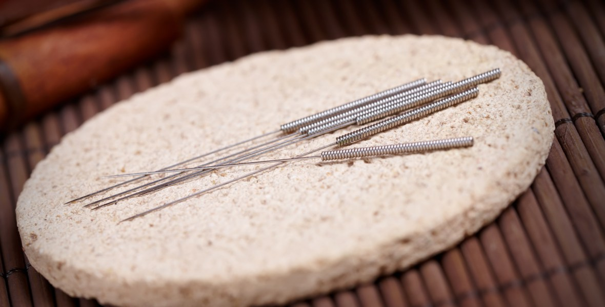Acupuncture needles laying on the stone mat, TCM Traditional Chinese Medicine concept photo representing Spot On Acupuncture in Edmonton