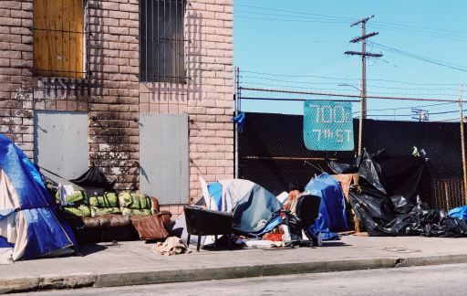 Homeless tent encampment on the sidewalk next to a building