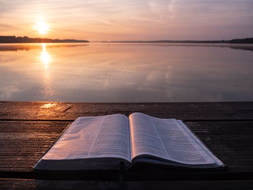 A bible on a table facing the shore just as the sun rises over the water.