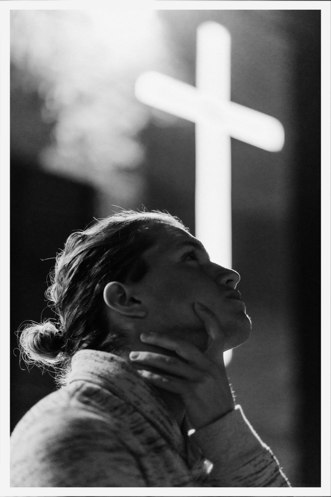 Black and white photo of a woman sitting in front of a lighted cross representing waiting for an answer to prayer.