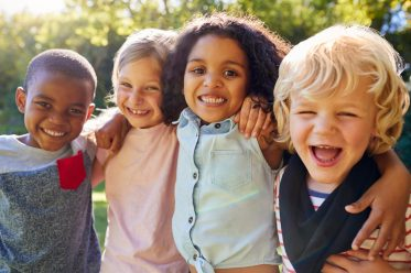 Photo of children of different ethnic groups smiling and hugging. Pic represents being unified in love.